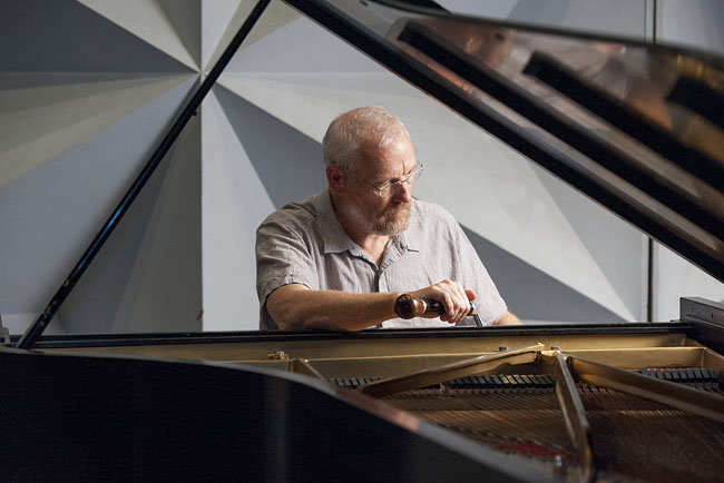 Peter Sumner, the principal concert piano technician, tunes a 9-foot Steinway concert grand on the Dinkelspiel stage.