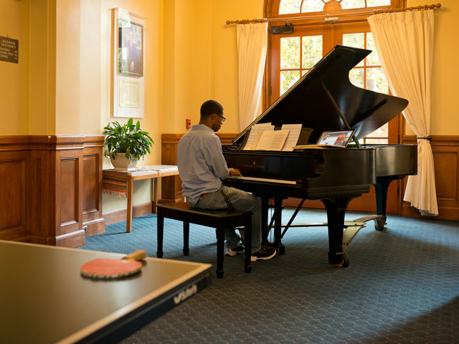 Junior Dewey Kemp practices preludes on a Steinway concert grand in the lounge of the Branner residence.