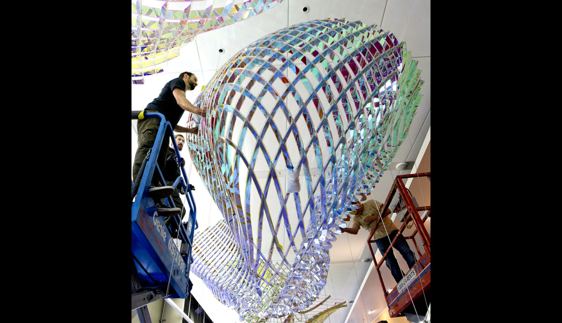 Workers install Three Fold, which hangs from the ceiling of the second floor of the Li Ka Shing Center for Learning and Knowledge. The sculpture, by artist Alyson Shotz, was dedicated May 21.