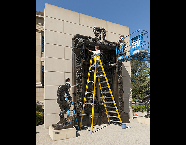 Coterm student and outdoor sculpture technician Bryce Cronkite-Ratcliff on ladder works with sculpture conservator Elizabeth Saetta to clean and reapply a protective wax to Auguste Rodin's 'Gates of Hell' at the Cantor Arts Center.