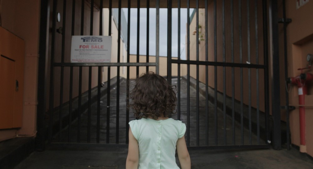 Still from the film My Aleppo features a girl facing a gate with a for sale sign