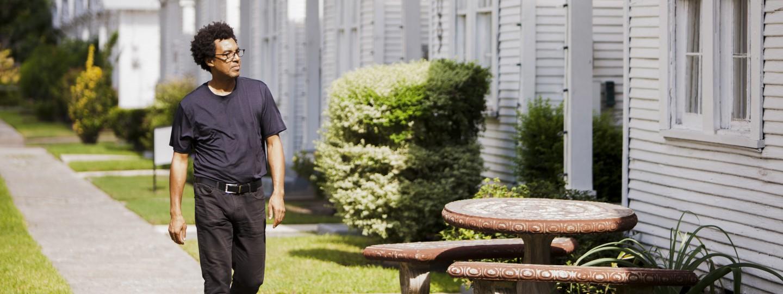 Artist Rick Lowe walking in front of row houses