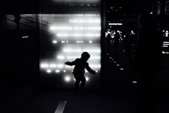 Black and white image of a child in silhouette against a wall with muted white lights.
