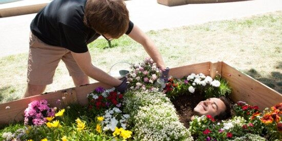 One student burying another in a flower bed as part of an interactive art project.