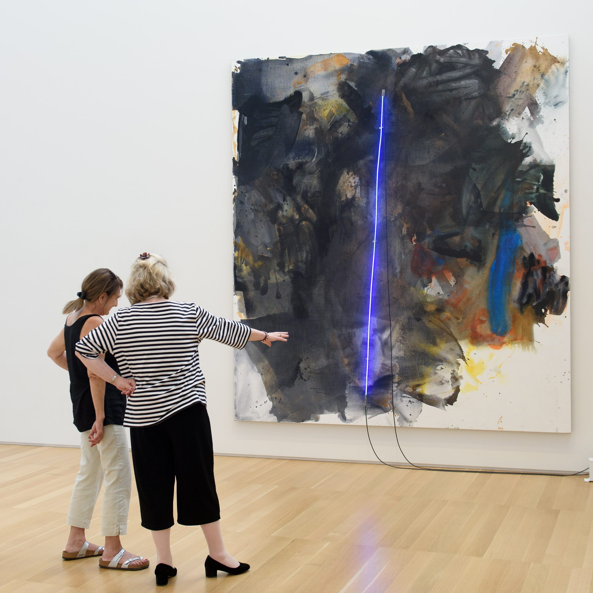 """Anderson Collection patrons Christine Nicholas and Julia Procopé stop to discuss the Mary Weatherford's, """"black painting"""" a gift of Debra and Steven Wisch'83, in honor of the Anderson family."""